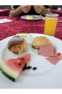 The last breakfast: Sweet bread, slice or watermelon, another piece of bread and mortadella.